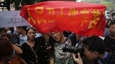 Des manifestants expriment leur colère à l'extérieur du bâtiment où les autorités chinoises tiennent une conférence de presse