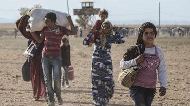 Des civils kurdes syrien franchissent la frontière avec la Turquie le 19 septembre 2014 près de Suruc dans la province Sanliurfa