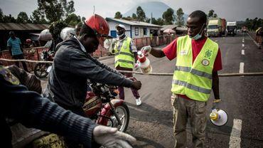 Un conduteur de moto-taxi se fait laver les mains sur la route entre Butembo et Goma, en RD Congo, dans le cadre de la lutte contre l'épidémie d'Ebola, le 16 juillet 2019