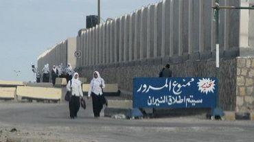 """De jeunes Egyptiennes passent devant une pancarte stipulant """"Interdiction de passer sous peine de tirs"""" à Al-Arish dans le Sinaï, le 17 novembre 2014"""