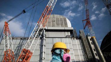 Un employé de Tepco marche devant le 3e réacteur de la centrale d'Okuma, dans la province de Fukushima, au Japon, le 31 janvier 2018