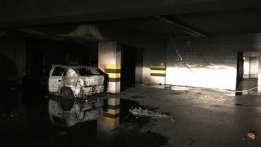 La voiture incendiée dans le parking des logements sociaux du quartier d'Aulne, à Ixelles