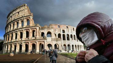 Un homme portant un masque de protection passe devant le Colisée à Rome le 7 mars 2020