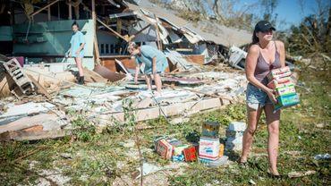 Une famille récupère des marchandises dans une boutique détruite leur appartenant, à Panama City le 11 octobre 2018.