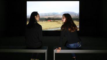 Des employées du musée Tate posent devant une image tirée du film de Charlotte Prodger, le 24 septembre 2018 à Londres