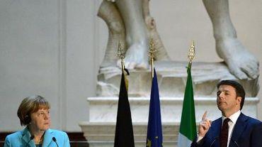 """Le chef du gouvernement italien Matteo Renzi prononce un discours à côté de la chancelière allemande Angela Merkel le 23 janvier 2015 dans la Galleria dell'Accademia, devant l'imposante sculpture du XVIème siècle """"David"""", de Michel-Ange"""