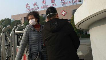 Une femme quitte le 12 janvier 2020 le centre médical de Wuhan où un homme est décédé d'une pneumonie appartenant à la même famille que le Sras