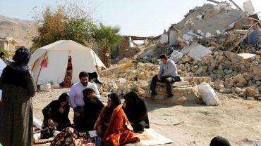 Des Iraniens assis devant leurs maisons en ruine après le séisme ayant frappé l'ouest de l'Iran, le 15 novembre 2017 dans le village de Kouik