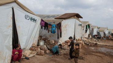 Des enfants joue devant la tête dans un camp de réfugiés à Idlib (Syrie).