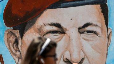 Une étudiante passe devant un portrait de l'ancien président vénézuélien Hugo Chavez, peint sur un mur, à Caracas le 29 janvier 2019