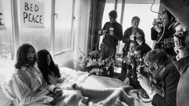 Beatles member John Lennon (L) and his wife Yoko Ono receive journalists 25 March 1969 in the bedroom of the Hilton hotel.