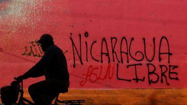 Un cycliste passe devant un graffiti réalisé au cours des manifestations contre le président Daniel Ortega, à Diriamba, à 40 km de Managua, le 124 juin 2018.