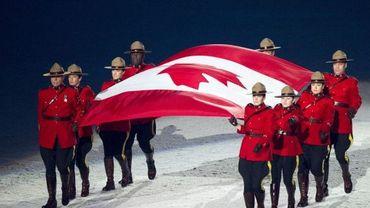 Des membres de la police montée canadienne portant le drapeau