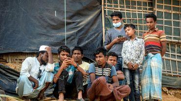 Des réfugiés Rohingyas regardent sur un téléphone portable le procès intenté à la Birmanie devant la Cour internationale de justice de La Haye, le 11 décembre 2019 dans un camp à Ukhia, au Bangladesh