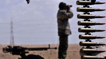 Un rebelle libyen prêt à l'offensive contre les forces pro-Kadhafi dans le désert près de la ville d'Ajdabiya