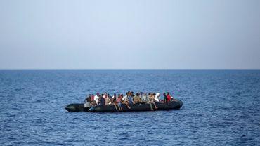 Des migrants attendent d'être secourus par les garde-côtes italiens près des côtes libyennes, le 6 août 2017