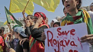 Des manifestants kurdes scandent des slogans et agitent leur drapeau national lors d'une manifestation contre l'offensive militaire turque dans le nord-est de la Syrie.