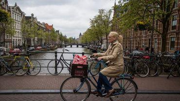 Une cyliste passe devant un canal à Amsterdam le 21 avril 2017