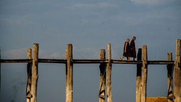 Des moines birmans sur un vieux pont de bois