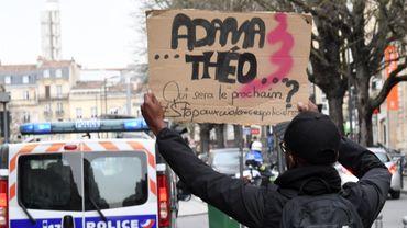 Un jeune homme brandissant une pancarte lors d'une manifestation contre les violences policières ce dimanche 12 février à Bordeaux