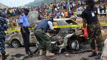 Des membres des servces de sécurité examinent le site de l'attentat d'Abuja le 2 mai