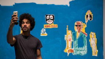"""Un homme fait un selfie devant la peinture """"King Zulu"""" de Jean Michel Basquiat."""