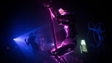 Un robot exécutent une chorégraphie autour d'une barre de pole dance, comme le font les danseuses dans un club nantais.