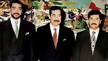Cette photo (non datée) montre Saddam Hussein entouré de ses fils Oudaï (à gauche) et Qoussaï (à droite) à Bagdad.