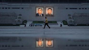 Des passants et des véhicules passent devant les portraits des derniers dirigeants nord-coréens Kim Il-Sung (à gauche) et Kim Jong-Il (à droite), le 21 juillet 2017, à Pyongyang.