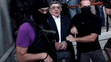 Nikos Michaloliakos entouré de policiers masqués à la sortie des locaux de la police le 28 septembre 2013 à Athènes