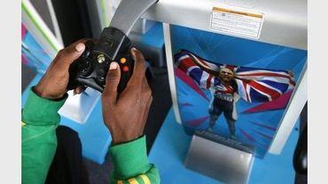 Lestrod Roland, athlète de Saint Kitts and Nevis, joue sur une console vidéo, le 22 juillet 2012 à Londres au village olympique
