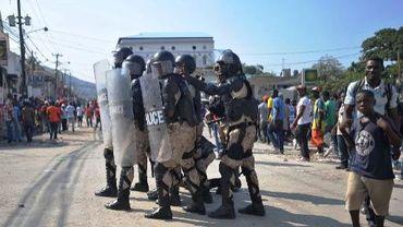 Des policiers anti-émeutes entre des manifestants pro et anti-gouvernementaux, à Port-au-Prince le 7 novembre 2013