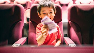 Portrait d'un petit garçon assis sur un fauteuil dans un cinéma avec des billets à la main, Shanghai, Chine