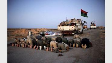 Des rebelles libyens prient sur la route de Syrte, près de Nofilia, le 29 août 2011