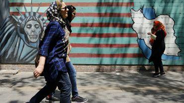 Des Iraniennes passent devant la façade de l'ancienne ambassade des Etats-Unis à Téhéran le 7 août 2018.