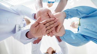 Équipe médicale empilant des mains