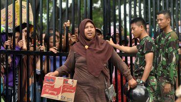 Une Indonésienne transporte un colis de nouilles instantanées reçu lors de la distribution d'aide à Palu en Indonésie le 9 octobre 2018