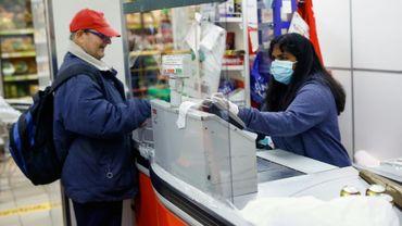 Une caissière portant un masque de protection dans un supermarché à Barcelone le 29 mars 2020