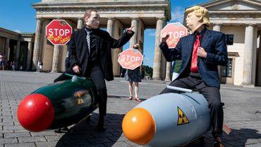 30 juillet 2020, Berlin : Deux militants déguisés en président américain et en président russe montent deux modèles de bombes nucléaires devant la Porte de Brandebourg.