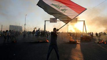 Un manifestant irakien agite le drapeau national irakien à Bagdad le 5 octobre 2019