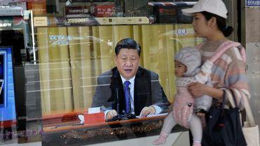 Une femme passe avec son bébé à Nouveau Taipei le 2 janvier 2019 devant une télévision montrant le président chinois Xi Jinping qui prononce un discours intransigeant envers Taïwan