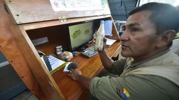 Un employé des services de l'environnement montre une bouteille remplie de sable, confisquée à un touriste à l'aéroport sur l'île de Baltra, dans l'archipel des Galapagos, le 17 juillet 2015