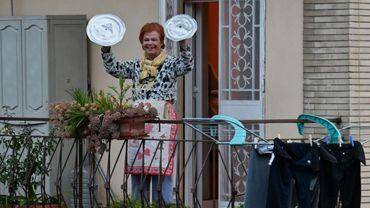 Une habitante de Rome participe à un concert improvisé depuis son balcon, utilisant des couvercles de casseroles comme cymbales, le 13 mars 2020