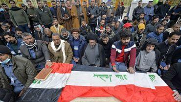 Des Irakiens prient sur le cercueil d'une victime du double attentat-suicide de Bagdad, en janvier 2021.