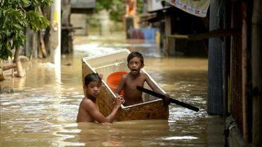 Des enfants dans une rue inondée le 18 décembre 2015 à Candaba aux Philippines