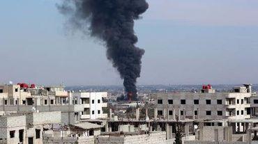 La fumée s'élève d'un immeuble attaqué par un raid aérien à Damas le 22 février 2014
