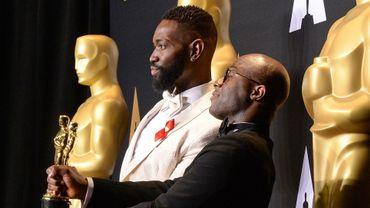 """Le réalisateur de """"Moonlight"""" Barry Jenkins (à droite) et son scénariste Tarell Alvin McCraney posent avec les Oscars du meilleur film et du meilleur scénario adapté"""