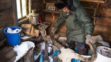 Prokopi Nogovitsyne montre le crâne d'un animal dans une cabane à l'arrière de sa maison en Iakoutie, le 27 novembre 2018