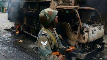 Un soldat indien patrouille devant un camion brûlé à Darjeeling le 17 juin 2017