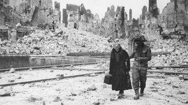 Un soldat américain aide une vieille dame en France en juin 44